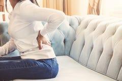 Vrouwelijke handen wat betreft rugpijnzitting in bank die thuis rusten jonge vrouwen lage taille gekwetste massage royalty-vrije stock fotografie