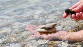 Vrouwelijke handenclose-up Een vrouw bouwt op haar palm een toren van stenen op de kust voort Het concept de bouw en stock footage