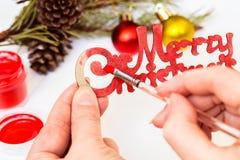 Vrouwelijke handenverf in rood op inschrijvings Vrolijke Kerstmis De decoratie van Kerstmis Royalty-vrije Stock Foto