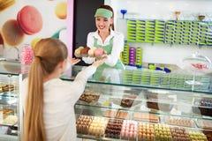 Vrouwelijke heerlijke macarons van de banketbakkersverkoop aan meisje Stock Afbeeldingen