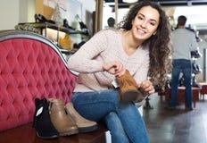 Vrouwelijke het kopen de winter vrouwelijke schoenen in schoenopslag stock foto