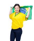 Vrouwelijke het voetbalventilators die van Azië de vlag van Brazilië houden Stock Afbeelding