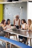 Vrouwelijke het werkcollega's die laptop computer in een vergadering met behulp van royalty-vrije stock foto's