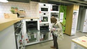 Vrouwelijke het winkelen moderne de opslagoven van meubilairikea, fornuis, keuken, stock footage