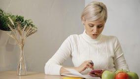 Vrouwelijke holdings slimme cellulair in handen en het maken van nota's in haar s stock video