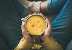 Vrouwelijke houdende mok soep van de pompoen de gele room in handen stock foto