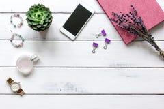 Vrouwelijke houten Desktop met smartphone en bloemen hoogste mening royalty-vrije stock foto's