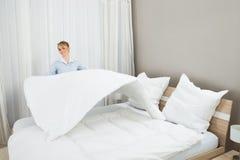 Vrouwelijke huishoudenarbeider die bed maken stock foto