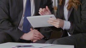 Vrouwelijke hulp tonende tablet aan directeur, samenkomende lijst en dagelijks programma stock videobeelden