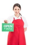 Vrouwelijke hypermarket arbeider die open teken houden Royalty-vrije Stock Foto's