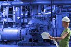 Vrouwelijke ingenieur met blauwdrukken op fabriek Royalty-vrije Stock Afbeelding