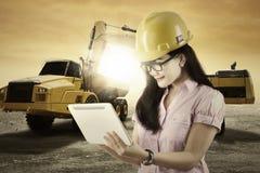 Vrouwelijke ingenieur met een graafwerktuig en een vrachtwagen Royalty-vrije Stock Foto