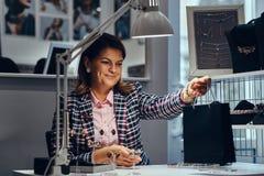 Vrouwelijke juwelenarbeider die achter het werklijst aankoop overhandigen aan klant in een opslag van luxejuwelen royalty-vrije stock foto