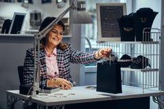 Vrouwelijke juwelenarbeider die achter het werklijst aankoop overhandigen aan klant in een opslag van luxejuwelen stock afbeelding