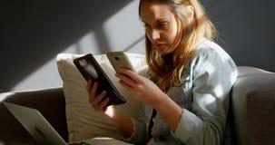 Vrouwelijke juwelenontwerper die mobiele telefoon en digitale tablet 4k gebruiken stock footage