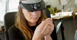 Vrouwelijke juwelenontwerper die in workshop 4k werken stock videobeelden