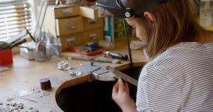 Vrouwelijke juwelenontwerper die in workshop 4k werken stock footage