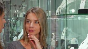 Vrouwelijke juwelier die haar vrouwelijke klant helpen die juwelen kiezen te kopen stock footage
