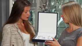 Vrouwelijke juwelier die mooie reeks in een doos tonen aan haar klant stock videobeelden