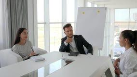 Vrouwelijke kandidaat tijdens baangesprek in groot bedrijf in wit en ruim bureau, dialoog op baan met secretaresse en stock videobeelden