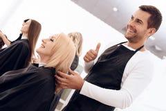 Vrouwelijke kapper die duimen tot rijpe vrouw met mooi kapsel tonen stock foto