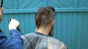 Vrouwelijke kapper die hipster mannelijk kapsel met haarscheerapparaat en kam maken in herenkapper op openlucht stock videobeelden