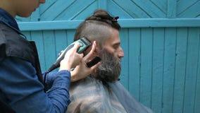 Vrouwelijke kapper die hipster mannelijk kapsel met haarscheerapparaat en kam maken voor de aantrekkelijke mens met binnen baard stock videobeelden