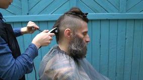 Vrouwelijke kapper die hipster mannelijk kapsel met haarscheerapparaat en kam maken voor de mens met baard in het kappen stock video