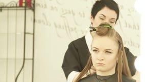 Vrouwelijke kapper die klem voor het bevestigen van haar tijdens het kappen in schoonheidssalon gebruiken Sluit herenkapper omhoo stock videobeelden