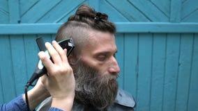 Vrouwelijke kapper die mannelijk kapsel met haarclipper maken in herenkapper op openlucht stock videobeelden