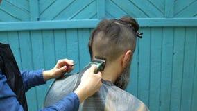 Vrouwelijke kapper die mannelijk kapsel met haarscheerapparaat en kam maken in herenkapper op openlucht stock videobeelden