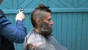 Vrouwelijke kapper die mannelijk kapsel met haarscheerapparaat maken in herenkapper op openlucht stock video