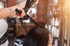 Vrouwelijke kapper die tot kapsel maken aan meisje in schoonheidssalon royalty-vrije stock afbeeldingen