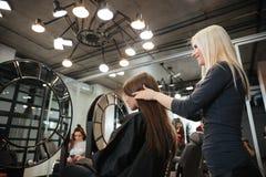 Vrouwelijke kapper die tot kapsel maken aan vrouw in salon royalty-vrije stock afbeelding