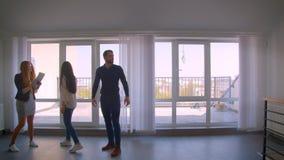 Vrouwelijke Kaukasische makelaar in onroerend goed die de flat tonen aan jong Kaukasisch paar stock video