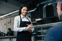 Vrouwelijke kelner in schort het schrijven orde stock foto