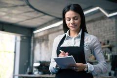 Vrouwelijke kelner in schort het schrijven orde Stock Foto's