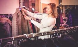Vrouwelijke klant die groen gewatteerd jasje onderzoeken royalty-vrije stock afbeelding