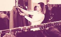 Vrouwelijke klant die groen gewatteerd jasje onderzoeken royalty-vrije stock fotografie