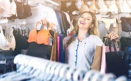 Vrouwelijke klant die haar aankopen in ondergoedwinkel opscheppen royalty-vrije stock fotografie