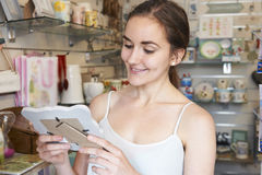 Vrouwelijke Klant die Omlijsting in Giftwinkel bekijken Stock Fotografie