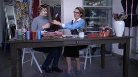 Vrouwelijke klant die textiel met naaister kiezen stock videobeelden