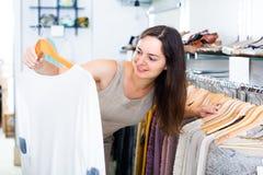 Vrouwelijke klant die trui kiezen bij opslag Stock Fotografie