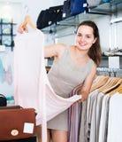 Vrouwelijke klant die trui kiezen bij opslag Stock Afbeelding