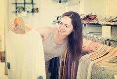 Vrouwelijke klant die trui kiezen bij opslag Stock Afbeeldingen