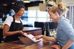 Vrouwelijke klant die wijn in een bar kiezen Royalty-vrije Stock Afbeeldingen