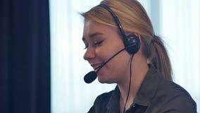 Vrouwelijke klantenondersteuningsexploitant met en hoofdtelefoon die spreken glimlachen stock video