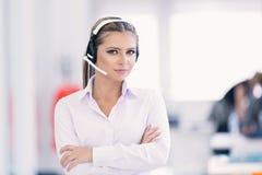 Vrouwelijke klantenondersteuningsexploitant met hoofdtelefoon en het glimlachen Royalty-vrije Stock Afbeeldingen