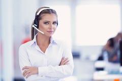 Vrouwelijke klantenondersteuningsexploitant met hoofdtelefoon en het glimlachen Royalty-vrije Stock Foto's