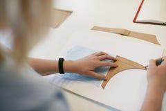 Vrouwelijke Kleermaker Making Sewing Patterns op Lijst stock afbeelding